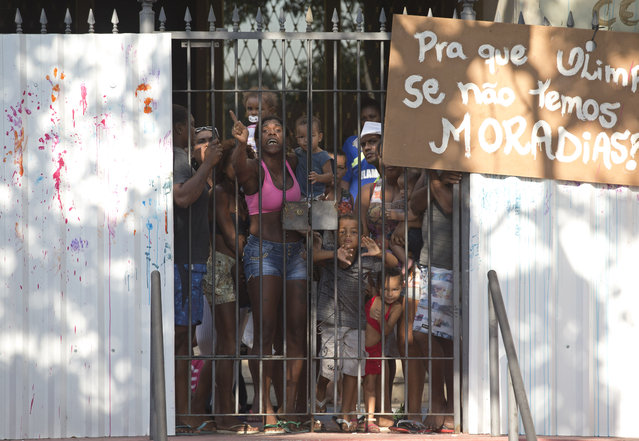 People stand behind a fence at a building they invaded about a week ago, before their eviction in the Flamengo neighborhood of Rio de Janeiro, Brazil, Tuesday, April 14, 2015. (Photo by Silvia Izquierdo/AP Photo)