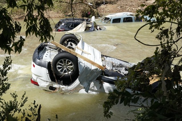 Vehicles come to rest in a stream Sunday, August 22, 2021, in Waverly, Tenn. (Photo by Mark Humphrey/AP Photo)