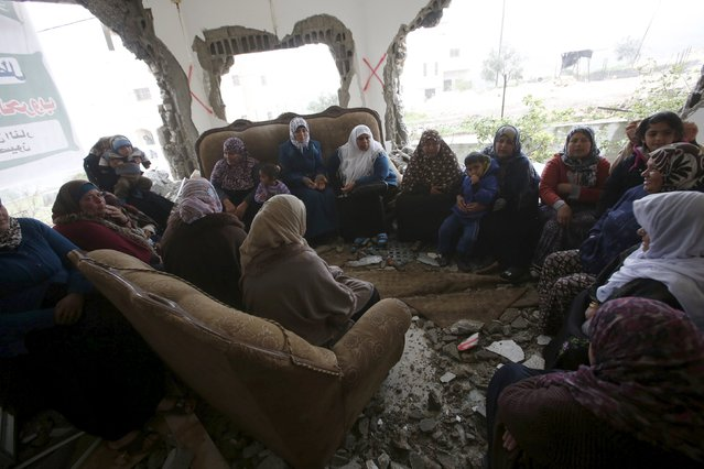 Palestinians gather in the home of Mohammed al-Haroub after it was partially demolished by Israeli army in the West Bank village of Dir Samt, south of Hebron February 23, 2016.  Israeli army bulldozers on Tuesday demolished the homes of two Palestinians who killed five people in attacks in the occupied West Bank and Israel last year, the military said. Mohammed al-Haroub shot at cars near an Israeli settlement bloc in the West Bank on Nov. 20, the military said, killing an Israeli, an American student and a Palestinian. (Photo by Mussa Qawasma/Reuters)