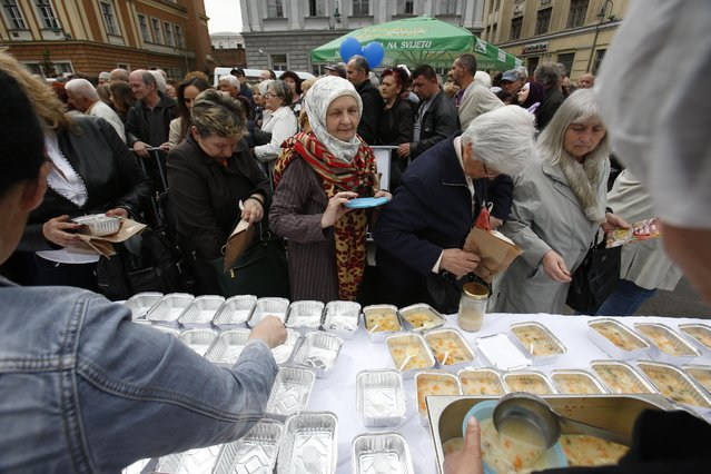 Bosnian people gather to taste chicken stew after cooks and volunteers prepared the stew in Sarajevo, on Friday April 17, 2015. (Photo by Amel Emric/AP Photo)