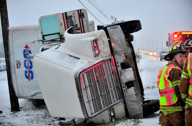 A tractor-trailer overturned in the 3900 block of Molly Pitcher Highway soussth of Chambersburg, Pa. during the year's first snowsstorm Thursday, January 2, 2014. The driver of the truck was not injured during the crash. Passersby helped the driver exit the cab. Slippery road conditions may have contributed to several accidents during the storm. (Photo by Markell DeLoatch/AP Photo/Public Opinion)