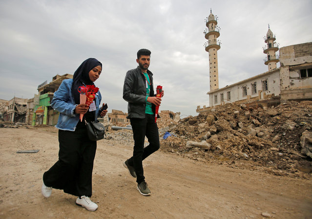 Members of a civil activist group distribute flowers on Valentine's Day in Mosul, Iraq on February 14, 2019. (Photo by Khalid al-Mousily/Reuters)