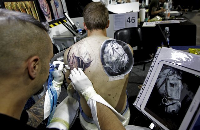 An artist draws a tattoo on a man's back during a tattoo convention in Ljubljana April 18, 2015. (Photo by Srdjan Zivulovic/Reuters)