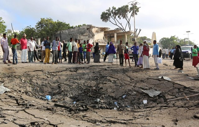 Residents gather at the scene of a car bomb attack near Somali Youth League Hotel, known as SYL hotel, in Hamarweyne district in Mogadishu, Somalia February 27, 2016. At least nine people were killed when fighters from Somali Islamist group al Shabaab set off a car bomb at the gate of a popular park and near the hotel in the capital, sending a plume of smoke above the coastal city. (Photo by Feisal Omar/Reuters)