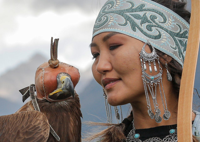 A Kyrgyz berkutchi (eagle hunter) holds her bird, a golden eagle, during the Solburun national hunt festival in the Kyrchyn gorge near Lake Issyk-Kul, 350 km from the country's capital of Bishkek, Kyrgyzstan, 30 August 2021. Salbuurun is a hunting game of the Kyrgyz people with hunting birds and dogs. In Kyrgyzstan, hunting with golden eagles is still a popular way to feed a family. (Photo by Igor Kovalenko/EPA/EFE)