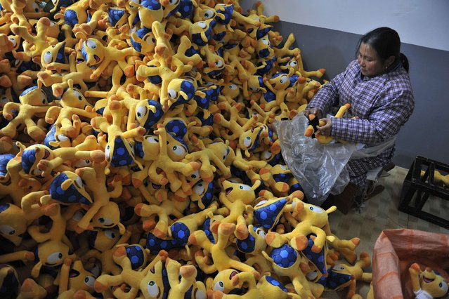This picture taken on January 6, 2014 shows a worker making a soft toy of Fuleco the Armadillo, the official mascot of the 2014 World Cup football tournament, at a factory in Tianchang, east China's Anhui province. (Photo by AFP Photo)