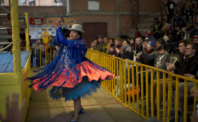 Veteran cholita wrestler Leydi Huanca, 29, dances as she enters the ring area to compete in El Alto, Bolivia, Sunday, February 10, 2019. As a match is about to start, cholita wrestlers apply makeup and perfume and then enter to ring dancing to folkloric music. (Photo by Juan Karita/AP Photo)