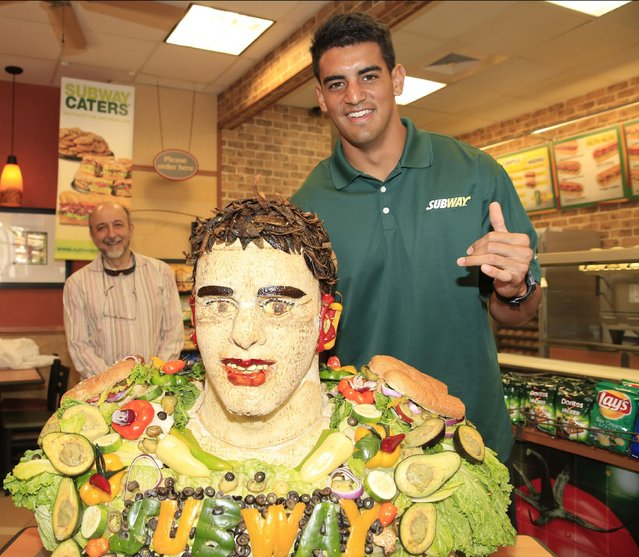 Marcus Mariota, 2015 draft prospect and newest SUBWAY Famous Fan, poses with a life-size food statue made of SUBWAY sandwich ingredients in his likeness, including new guacamole, on Wednesday, April 22, 2015, in Honolulu. Mariota joins a roster of SUBWAY Famous Fans including Clayton Kershaw, Mike Trout, Pele, Nastia Liukin, and Robert Griffin III. (Photo by Marco Garcia/Invision for SUBWAY/AP Images)