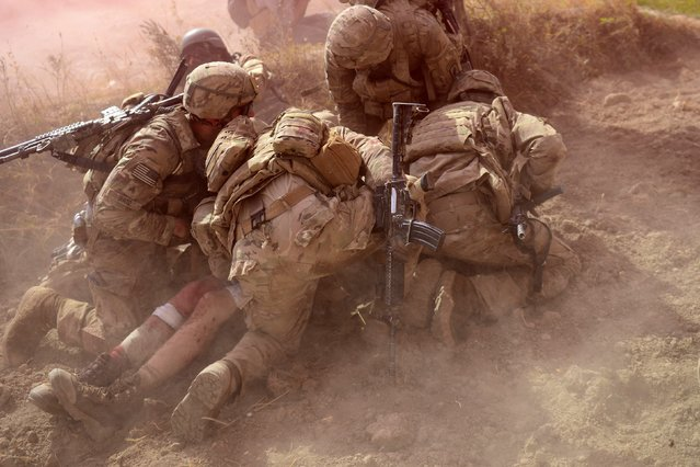 US Army soldiers attached to 2nd platoon, C troop, 1st Squadron (Airborne), 91st U.S Cavalry Regiment, 173rd Airborne Brigade Combat Team operating under NATO sponsored International Security Assistance Force (ISAF) protect a wounded comrade from dust and smoke flares after an Improvised Explosive Device (IED) blast during a patrol near Baraki Barak base in Logar Province on October 13, 2012. (Photo by Munir Uz Zaman/AFP Photo)