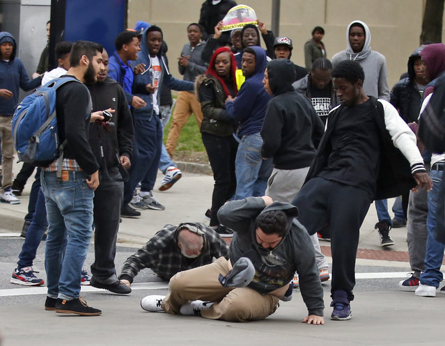 A man is kicked as he attempts to get up after being knocked down, following a march to City Hall for Freddie Gray, Saturday, April 25, 2015 in Baltimore. (Photo by Alex Brandon/AP Photo)