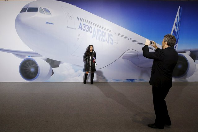 Visitors take pictures in front of an image of an Airbus A330 plane at a ground-breaking ceremony for the Airbus A330 completion and delivery center in Tianjin, China, March 2, 2016. (Photo by Kim Kyung-Hoon/Reuters)