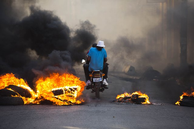 People on a motorcycle drive past a burning roadblock placed by anti-government protesters who are demanding the resignation of Haitian President Jovenel Moise, near the presidential palace in Port-au-Prince, Haiti, Wednesday, February 13, 2019. Protesters are angry about skyrocketing inflation and the government's failure to prosecute embezzlement from a multi-billion Venezuelan program that sent discounted oil to Haiti. (Photo by Dieu Nalio Chery/AP Photo)