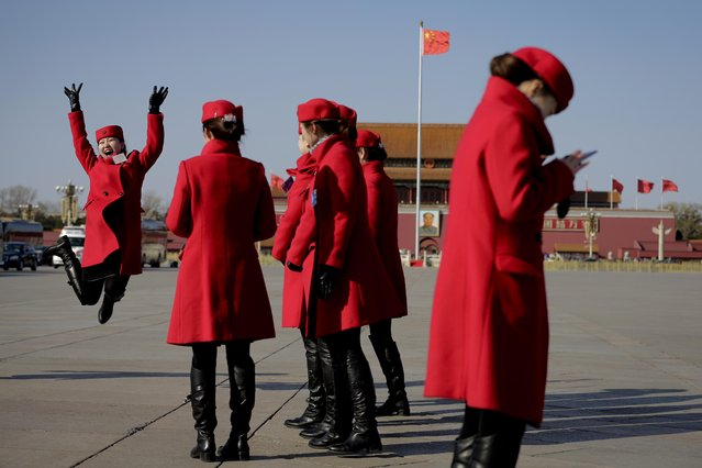 A Chinese bus ushers jump as she pose for a photograph on Tiananmen Square during a plenary session of the National People's Congress held at the Great Hall of the People in Beijing, Wednesday, March 9, 2016. (Photo by Andy Wong/AP Photo)