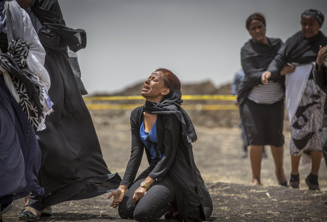 Ethiopian relatives of crash victims mourn and grieve at the scene where the Ethiopian Airlines Boeing 737 Max 8 crashed shortly after takeoff on Sunday killing all 157 on board, near Bishoftu, south-east of Addis Ababa, in Ethiopia Thursday, March 14, 2019. The French air accident investigation authority said Thursday that it will handle the analysis of the black boxes retrieved from the crash site and they have already arrived in France but gave no time frame on how long the analysis could take. (Photo by Mulugeta Ayene/AP Photo)