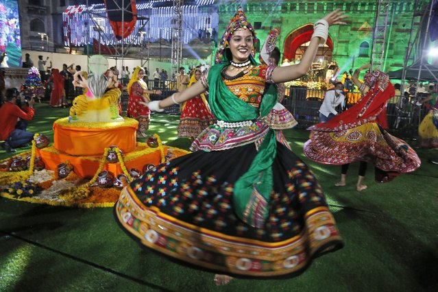 Indians wearing traditional attire perform the Garba, a dance of Gujarat state, to celebrate the Hindu festival Navratri in Ahmedabad, India, Thursday, October 7, 2021. (Photo by Ajit Solanki/AP Photo)