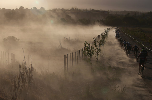 Cyclists kick up dust as they ride in the early morning light in the early part of the 108km Stage 1 of the 2016 ABSA Cape Epic mountain bike race in Saronsberg  South Africa on March 14, 2016. The ABSA Cape Epic is often described as the 'Tour de France' of mountain biking and will see 1,200 riders racing over 652km in eight stages and 15,100m of climbing. UCI professional racers ride alongside amateur riders during the eight day long race. (Photo by Kim Ludbrook/EPA)
