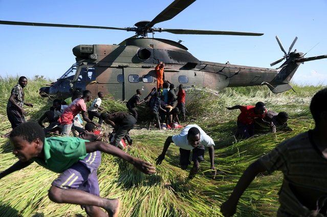 People run after collecting food aid from a South African National Defence Force (SANDF) helicopter in the aftermath of Cyclone Idai in Nhamatanda village, near Beira, Mozambique, March 26, 2019. (Photo by Siphiwe Sibeko/Reuters)