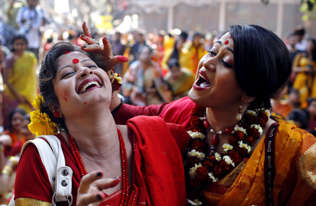 Bangladeshi girls put vermillion powder on each other as they celebrate the arrival of spring on the first day of Falgoon at the Dhaka University campus in Dhaka, Bangladesh, Thursday, February 13, 2014. Falgoon is the eleventh month in Bengali calendar. (Photo by A. M. Ahad/AP Photo)