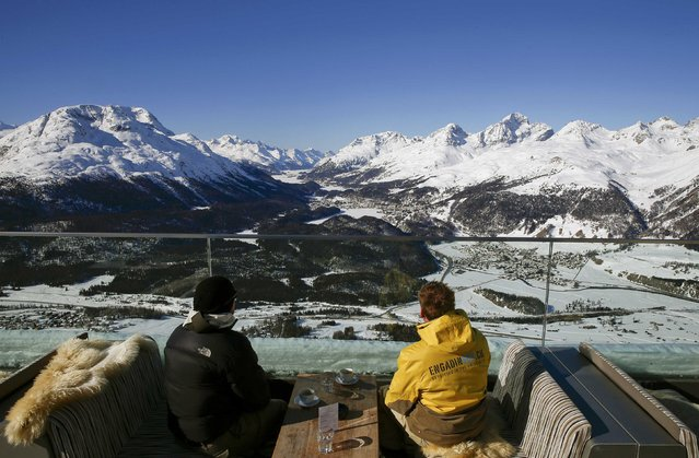 Two men enjoy a sunny winter's day on the terrace of a restaurant at the Muottas Muragle mountain near the resort of St. Moritz, Switzerland March 18, 2016. St. Moritz, seen in the center background, hosts the FIS Ski World Cup Finals from March 16 to 20. (Photo by Arnd Wiegmann/Reuters)