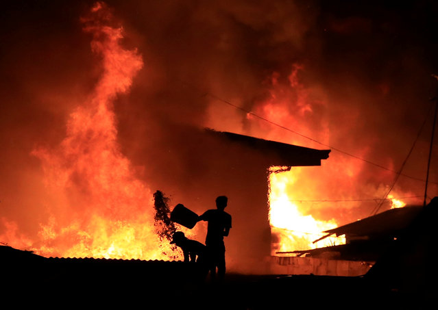 A resident throws a bucket of water at burning shanties at a community of informal settlers engulfed by a fire in Catmon, Malabon city, metro Manila, Philippines February 8, 2017. (Photo by Romeo Ranoco/Reuters)