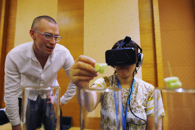 Dan Garrett of the Royal College of Art and Imperial College London watches as a visitor tastes food using Tasteworks technology, a Virtual Reality experience that augments and stimulates taste, during a design competition showcase of wearable technology at the Augmented Human International Conference in Singapore March 10, 2015. (Photo by Edgar Su/Reuters)