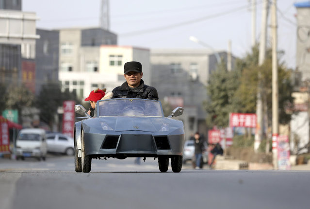 Guo, a farmer in his 50s, drives his self-made scale replica of a Lamborghini with his grandson on a street in Zhengzhou, Henan province February 19, 2014. (Photo by Reuters/China Daily)