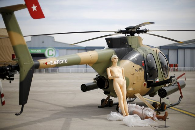 Mannequins lie next to a helicopter ahead of the International Air and Space Fair (FIDAE) at Santiago international airport, March 28, 2016. (Photo by Ivan Alvarado/Reuters)
