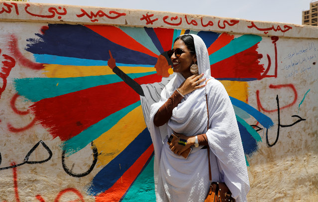 Alaa Salah, a Sudanese protester whose video gone viral and make her an icon for the mass anti-government protests, stands in front of a mural depicting her in front of the Defence Ministry in Khartoum, Sudan, April 20, 2019. (Photo by Umit Bektas/Reuters)