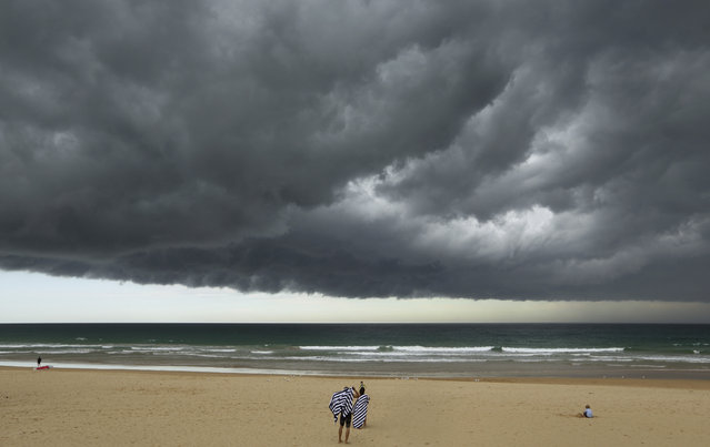 A storm cloud passes over bathers who prepare to leave Sydney's Manly Beach during an afternoon storm March 5, 2014. The storm, which generated little rain but high gusts of wind, was blown out to sea. (Photo by Will Burgess/Reuters)