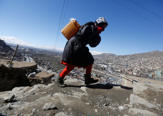 An Afghan girl carries water on her back as she climbs a hill in Kabul, Afghanistan February 20, 2017. (Photo by Omar Sobhani/Reuters)