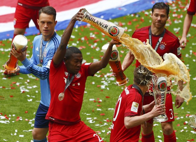 Bayern Munich's David Alaba (L) pours beer over Mitchell Weiser after their final German first division Bundesliga soccer match of the season against FSV Mainz 05 in Munich, May 23, 2015. (Photo by Michaela Rehle/Reuters)
