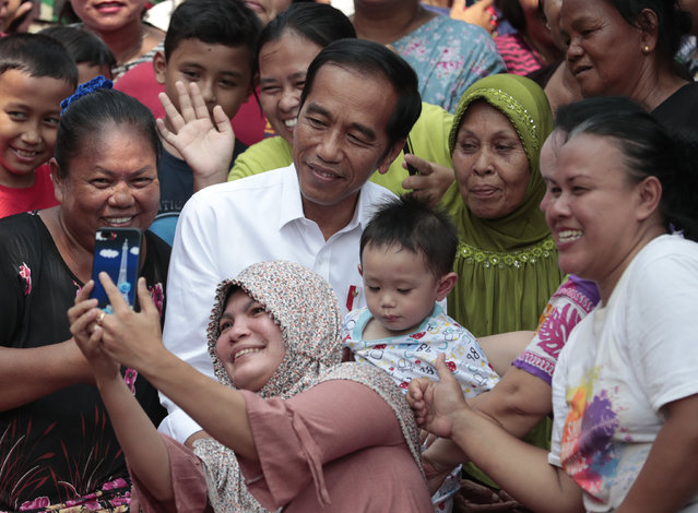 Residents take a selfie with incumbent Indonesian President Joko Widodo, center, prior to a speech declaring his victory in the country's presidential election, at a slum in Jakarta, Indonesia, Monday, Tuesday, May 21, 2019. Indonesian President Joko Widodo has been elected for a second term, official results showed, in a victory over a would-be strongman who aligned himself with Islamic hard-liners and vowed Tuesday to challenge the result in the country's highest court. (Photo by Dita Alangkara/AP Photo)