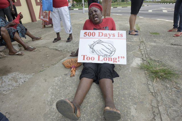 """A member of Bring Back Our Girls movement csits on the ground with a plarcard as she and others press for the release of the missing Chibok schoolgirls in Lagos, on April 14, 2016. Nigeria's government said it was studying a """"proof of life"""" video showing 15 of the more than 200 schoolgirls abducted by Boko Haram, as parents and their supporters marked the second anniversary of the kidnapping. A total of 276 girls were abducted from the Government Girls Secondary School in Chibok, northeast Nigeria, on April 14, 2014. Fifty-seven escaped in the immediate aftermath. (Photo by Pius Utomi Ekpei/AFP Photo)"""