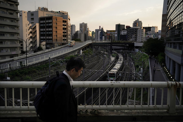 In this Wednesday, May 22, 2019, photo, a man walk on the bridge as a Yamanote Line train departs from Ikebukuro Station in Tokyo. Operated by the East Japan Railway Co., the Yamanote Line in Tokyo makes a loop around the center of the city, connecting 29 stations that include key stops such as Shinjuku, Shibuya and Ikebukuro. A complete loop of about an hour offers scenes of Japanese daily lives: jam-packed morning commute, views of the famous Shibuya crossing, high-rises, downtown shopping arcades, and a quick break at a noodle stand. (Photo by Jae C. Hong/AP Photo)