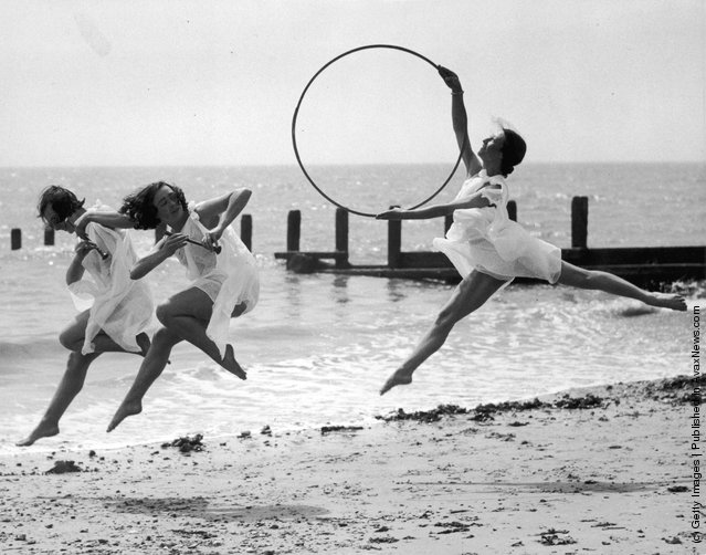 1935: Three members of a dance school rehearse for an upcoming performance on the beach at Worthing. One dancer with a hoop pursues two others with small pipes
