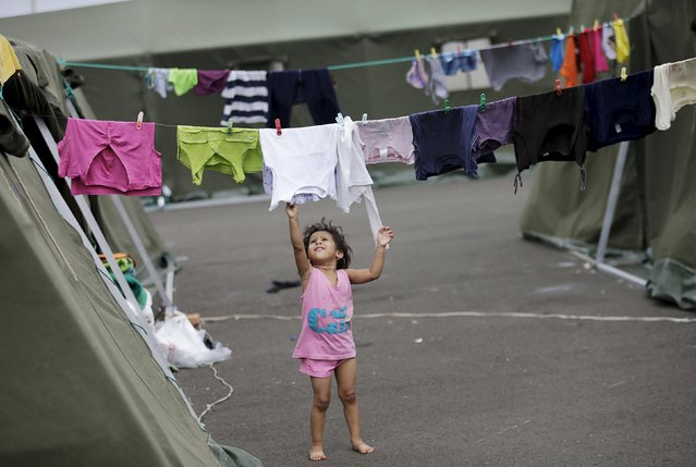 A girl is pictured next to a line of clothes hung out to dry outside a tent at the Reales Tamarindos airport which is used as a shelter, after being evacuated from her home in Portoviejo, after an earthquake struck off Ecuador's Pacific coast, April 22, 2016. (Photo by Henry Romero/Reuters)