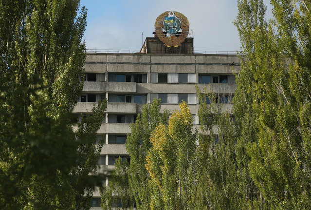A Soviet-era hammer and sickle adorned with a Ukrainian flag stands on top of an abandoned apartment building on September 30, 2015 in Pripyat, Ukraine. (Photo by Sean Gallup/Getty Images)