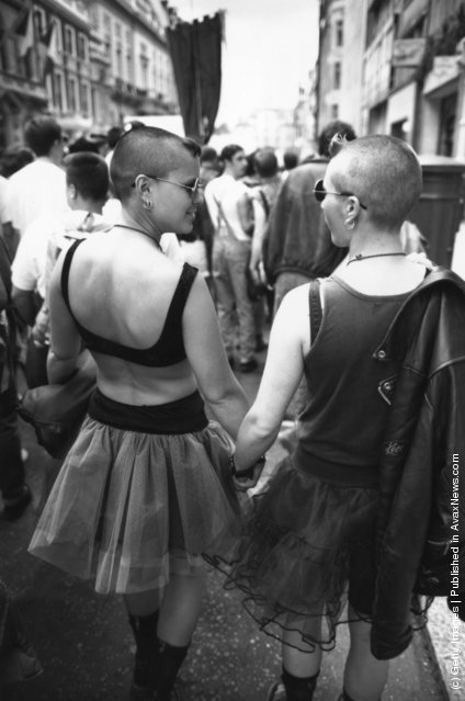 A lesbian couple hold hands during the annual Gay Pride march through central London, July 1993