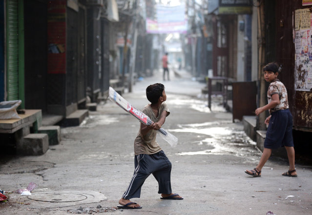 A kid tests his new bat, still wrapped in plastic, as he prepares to go out to play cricket, in Amritsar, India, 04 August 2019. Cricket is the most popular sport, played and watched, in India. (Photo by Raminder Pal Singh/EPA/EFE)