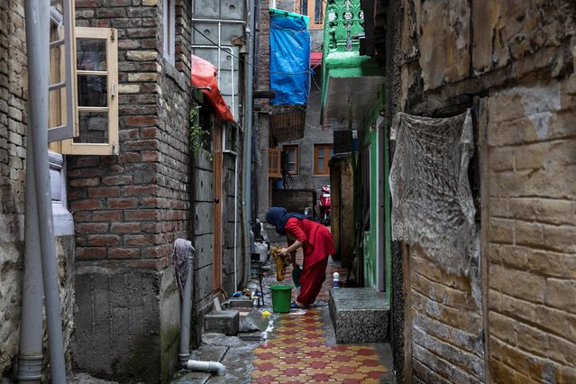 Kashmiri woman washes clothes in an alley during restrictions after the scrapping of the special constitutional status for Kashmir by the government, in Srinagar, August 14, 2019. (Photo by Danish Siddiqui/Reuters)