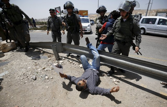 A Palestinian protester falls on the ground after being pushed by Israeli border policemen during a protest marking the first anniversary of the killing of 16-year-old Palestinian Mohammed Abu Khudair, who was burnt in Jerusalem in a suspected revenge attack for the kidnapping and slaying of three Israeli teens last year, near the West Bank city of Ramallah July 2, 2015. (Photo by Mohamad Torokman/Reuters)