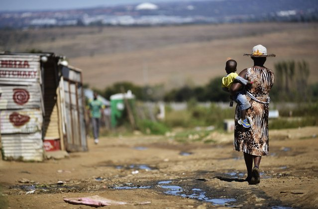 A woman carries her child as she walks alongside a line of shacks in the impoverished township of Diepsloot on the outskirts of Centurion on April 24, 2014. South Africans will mark 20 years of democracy since the first post-Apartheid election on April 27, 1994. (Photo by Mujahid Safodien/AFP Photo)