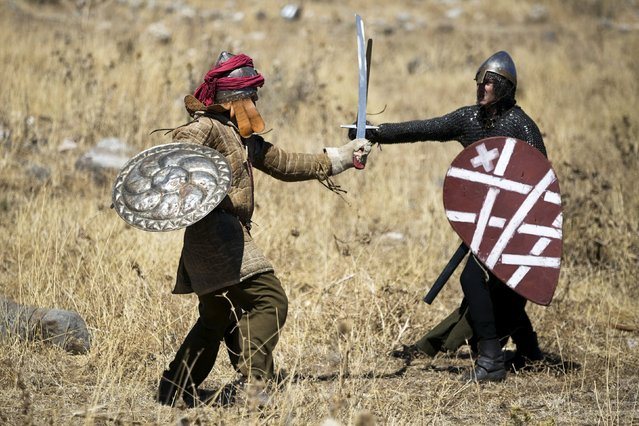 Enthusiasts wearing costumes fight during a re-enactment of a decisive Crusaders battle in northern Israel's Galilee region July 4, 2015. (Photo by Amir Cohen/Reuters)