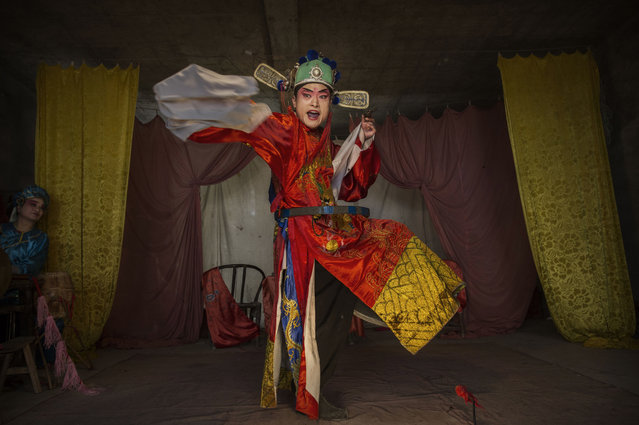 Sichuan Opera performer Wu Yonghong, 26 years, of the Jinyuan Opera Company performs for villagers at the Dongyue Temple on May 2, 2016 in Cangshan, Sichuan province, China. Sichuan opera is a vibrant, centuries-old tradition that showcases the joys and challenges of daily life in rural China with tales of love, tradition, and family honor. As the traditional audience grows older, the opera as a form of art and recreation is struggling to endure as newer spectators within younger generations are leaving the countryside for China's cities to seek employment. (Photo by Kevin Frayer/Getty Images)