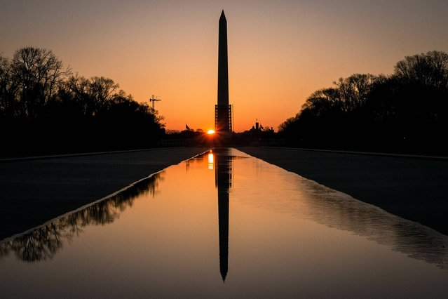 The sun peeks through the scaffolding around the Washington Monument at dawn in Washington, Monday, March 24, 2014. The National Park Service has announced they will reopen the earthquake damaged structure in May. (Photo by J. David Ake/AP Photo)