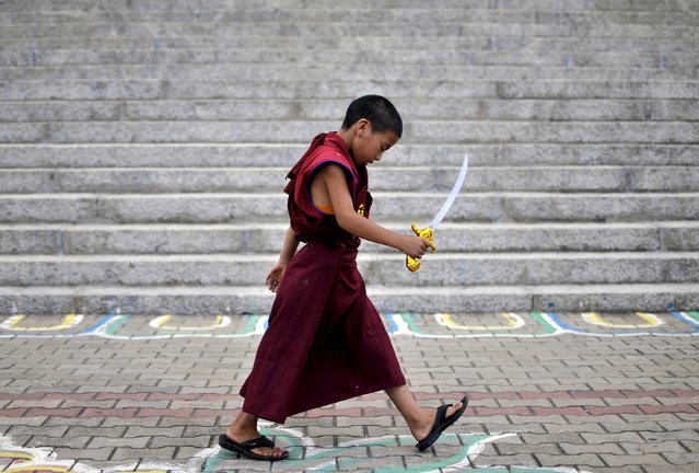 A novice Tibetan monk walks while holding a toy sword as he attends celebrations marking the 80th birthday of the Tibetan spiritual leader, the Dalai Lama, at the Sera Jey Monastery in Bylakuppe in the southern state of Karnataka, India, July 6, 2015. (Photo by Abhishek N. Chinnappa/Reuters)
