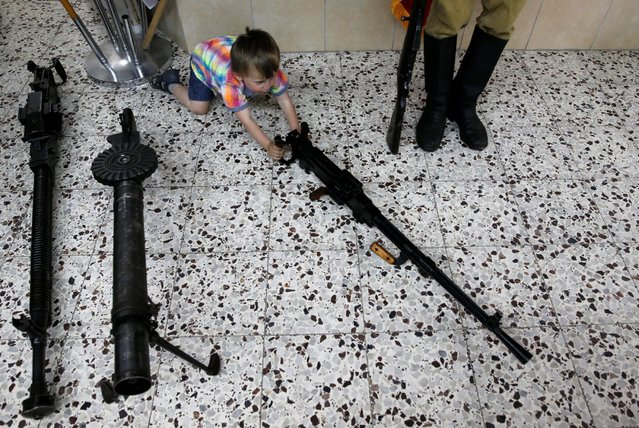 A boy plays with a machine gun during an event in remembrance of the upcoming Victory Day, marking the anniversary of the Allied victory over Nazi Germany, in the southern city of Ashdod, Israel, May 7, 2016. (Photo by Amir Cohen/Reuters)