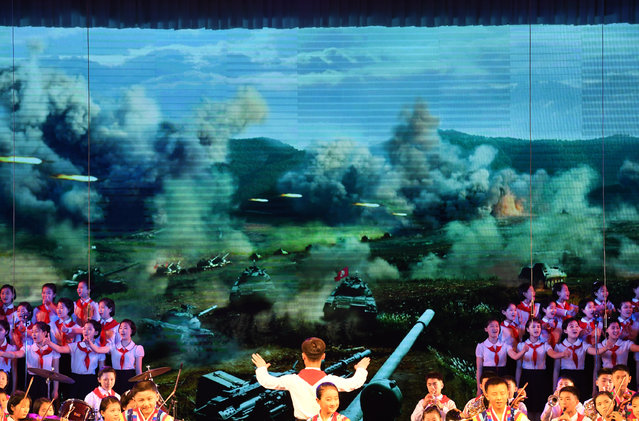 Young children perform a patriotic orchestra in front of patriotic images of missiles and tank ground assaults in the background at the Mangyongdae Children's Palace in Pyongyang, North Korea on May 5, 2016. Mangyongdae is a public facility managed by Korean Youth Corps in North Korea where pioneer members can engage in extra-curricular activities, such as learning music, foreign languages, computing skills and sports.   The pioneer movement is an organization for children operated by the communist party. (Photo by Linda Davidson/The Washington Post)