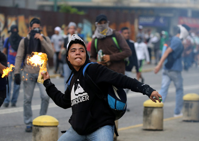 A demonstrator throws a molotov cocktail while clashing with riot police during a rally against Venezuela's President Nicolas Maduro's government in Caracas, Venezuela April 10, 2017. (Photo by Carlos Garcia Rawlins/Reuters)