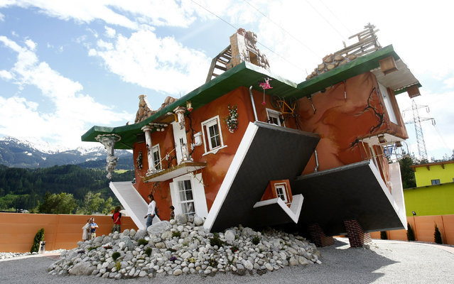 People walk out of a house, which was built upside down by Polish architects Irek Glowacki and Marek Rozanski, in the western Austrian village of Terfens May 5, 2012. The project is meant to serve as a new tourist attraction in the area, and is now open for public viewing. (Photo by Dominic Ebenbichler/Reuters)